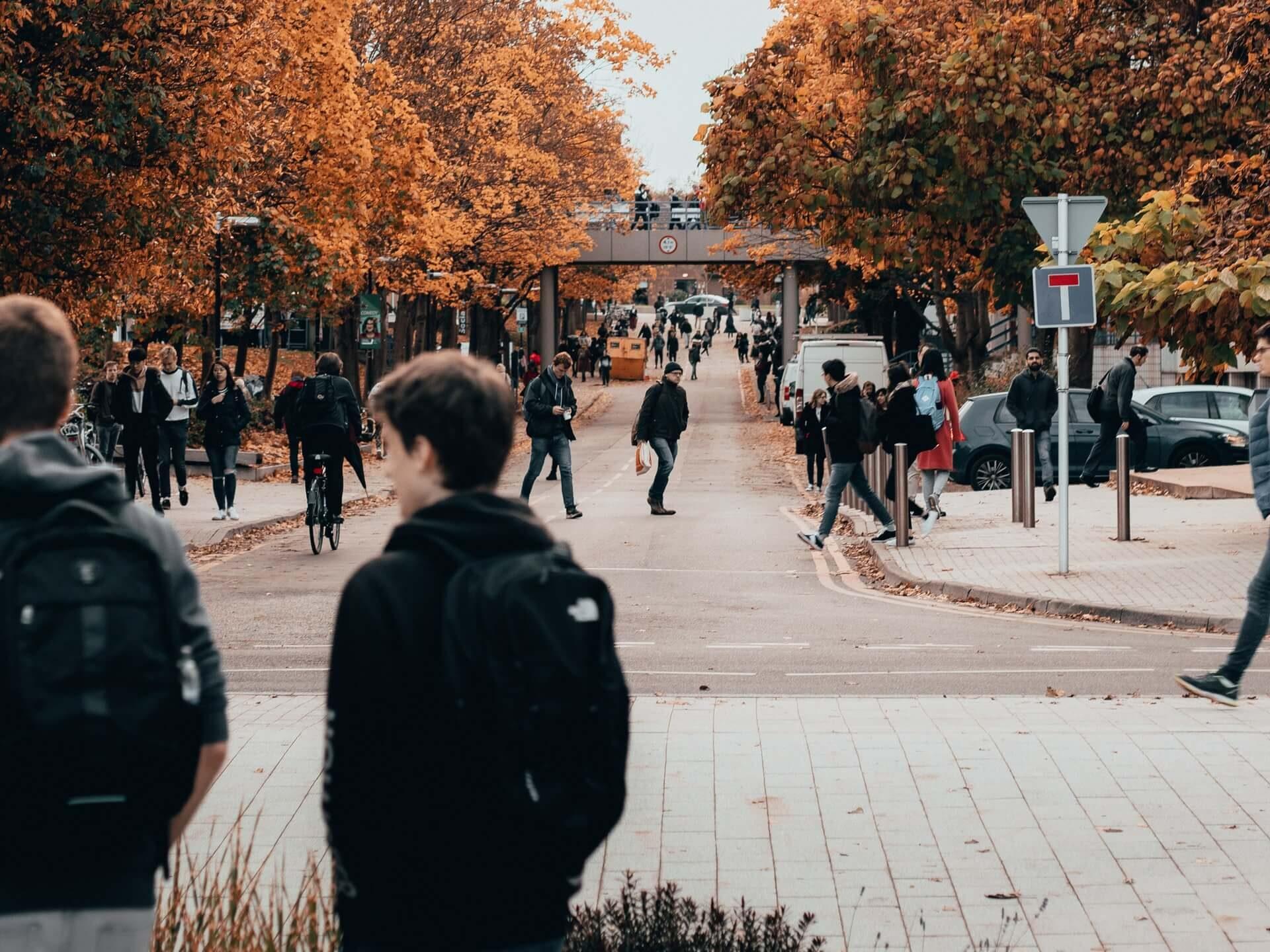 Diákok hátizsákokkal gyalogolnak és bicikliznek az utcán.