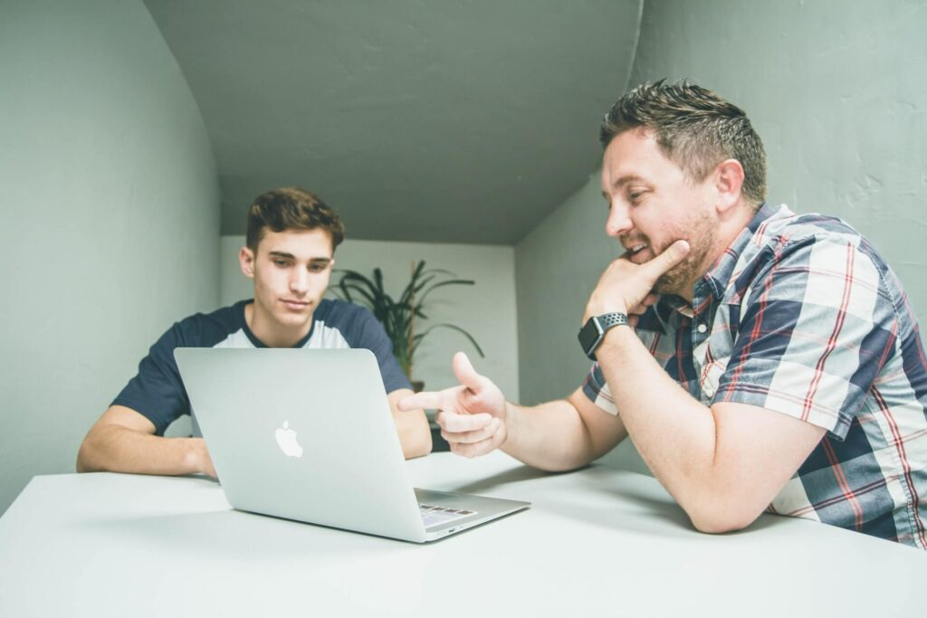 Egy férfi a MacBookra mutat, míg egy másik férfi figyel.