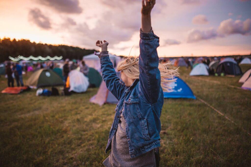 Szőke fiatal nő táncol egy fesztiválon, a háttérben sátrak és naplemente.