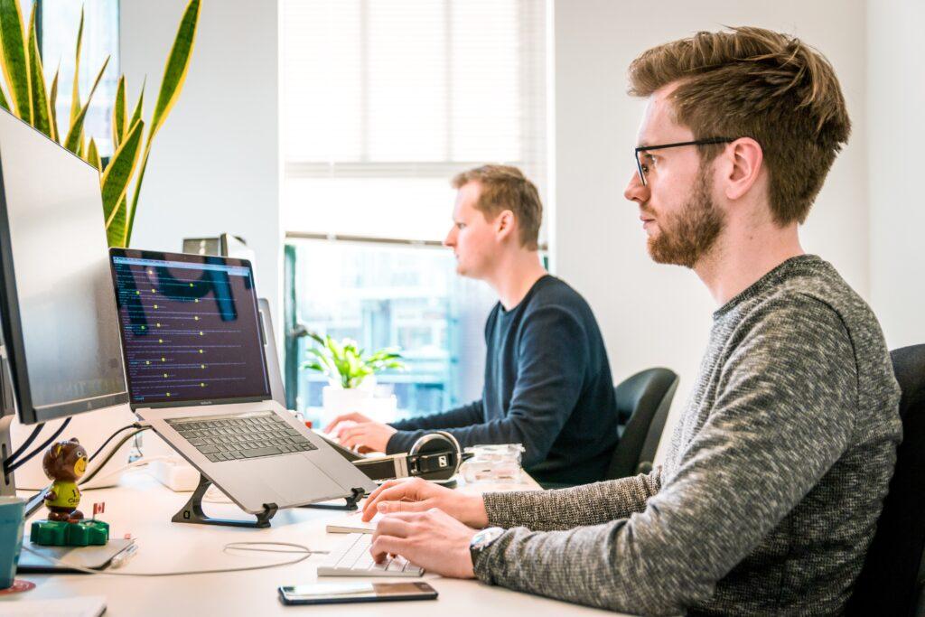 Két férfi dolgozik egy irodában, előttük laptopok és monitorok.