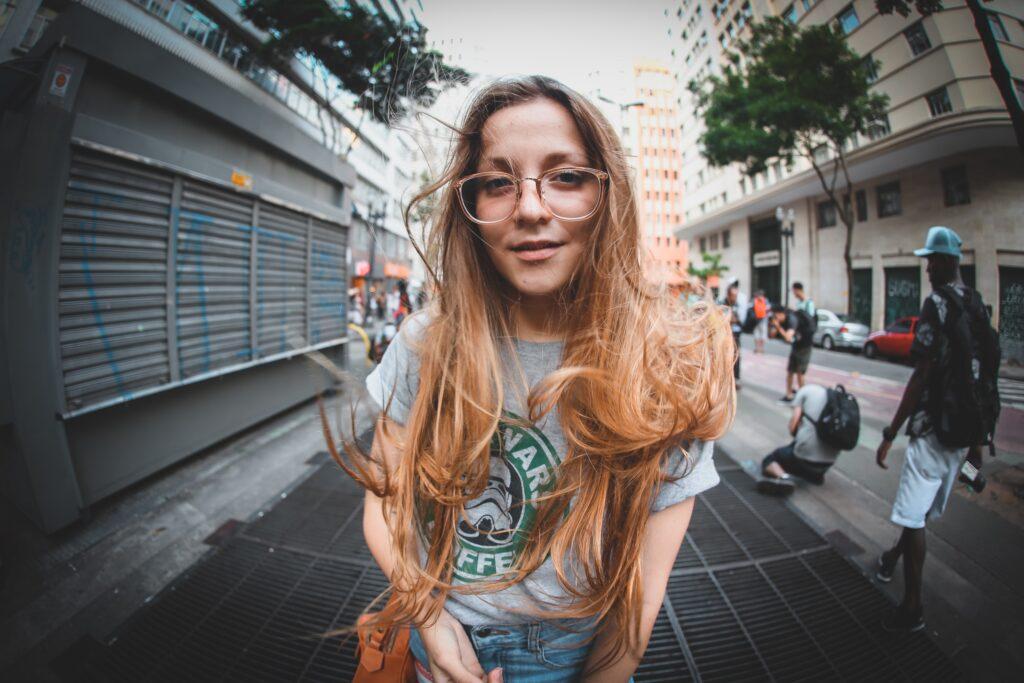 Vörös hajú lány szürke pólóban az utcán.